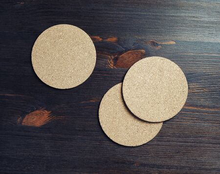 Photo of three blank cork beer coasters on wooden background. Stockfoto