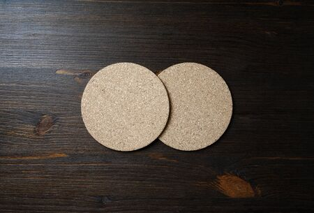 Photo of two blank cork beer coasters on wooden background. Flat lay. Stockfoto