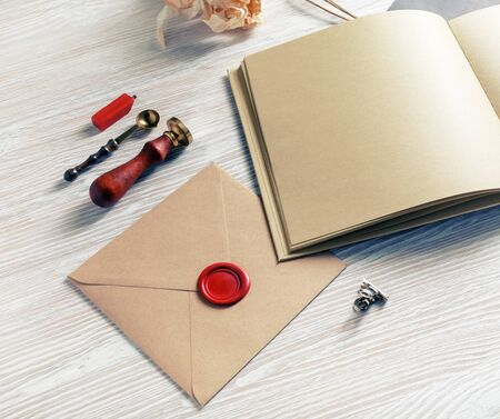 Blank retro stationery on light wooden background. Envelope with wax seal, stamp, book and spoon.