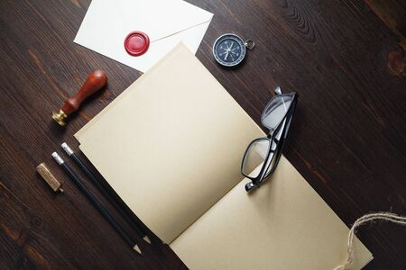Kraft paper book and retro stationery on wood table background. Branding mock up. Flat lay. Stockfoto