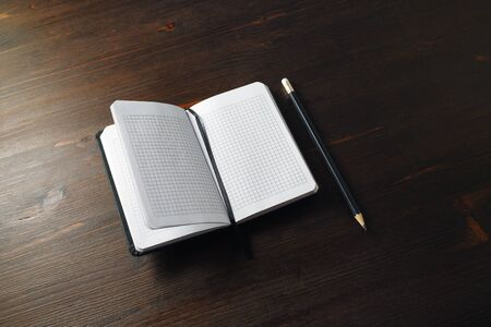 Opened blank notebook and pencil on wood table background. Copy space for text.