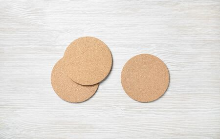 Photo of three blank cork beer coasters on light wooden background. Flat lay. Stock fotó