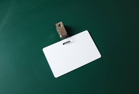 Blank ID card. White plastic badge on green blackboard background. Copy space for text. Responsive design template. 스톡 콘텐츠