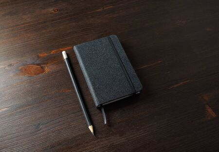Photo of black notepad and pencil on wood table background. 스톡 콘텐츠