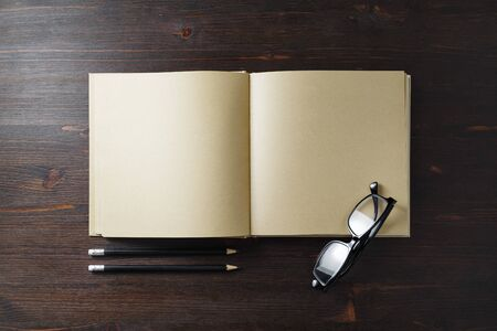 Blank kraft paper book, glasses and pencils on wood table background. Responsive design template. Flat lay.