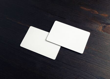 Two blank business cards on wood table background. Mockup for branding identity.