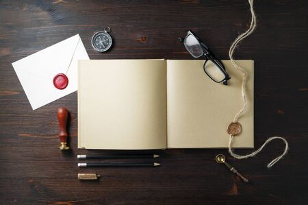 Photo of book with blank kraft paper pages and vintage stationery on wooden background. Flat lay.