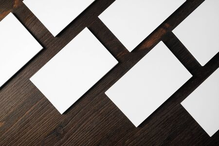 Blank white business cards on wooden background. Mockup for branding identity. Flat lay.