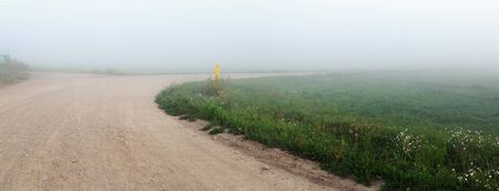 Gravel road turning in the fog. Morning in the countryside. Rural landscape. Panoramic shot. 스톡 콘텐츠