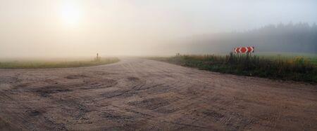 Gravel road and fog. Rural landscape. Panoramic shot