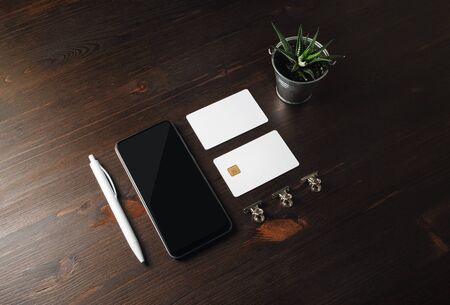 Blank branding template. Smartphone, credit cards, plant and pen on wood table background.