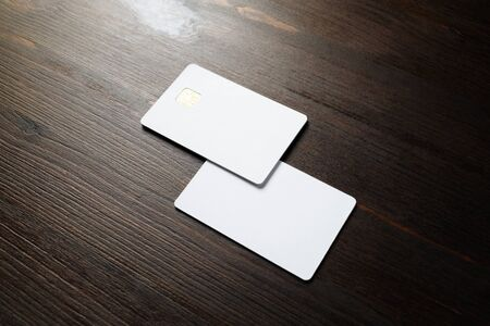 Photo of two blank credit cards on wood table background. White bank cards.