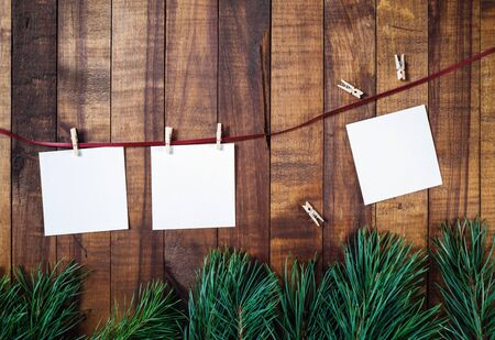 Blank notes or photos, clothespins, rope and pine branches on wooden background. Stationery template. Flat lay.