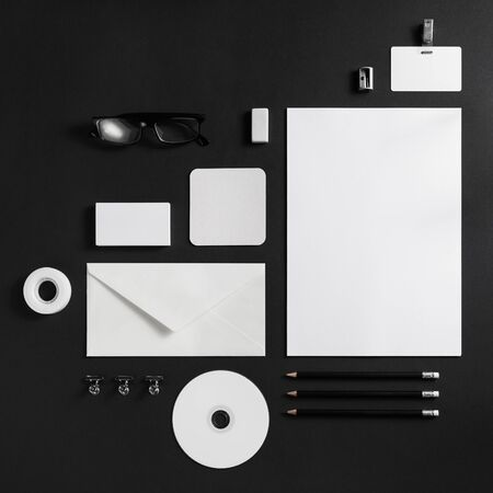 Blank branding identity set on black paper background. Corporate stationery template. Flat lay.