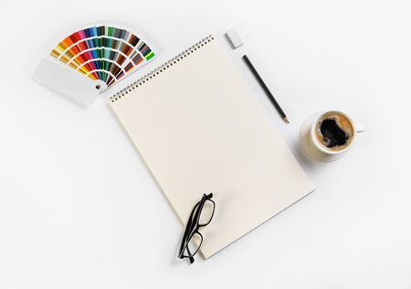 Blank stationery set. Sketchbook, color palette, glasses, coffee cup, pencil and eraser. Flat lay.