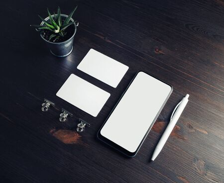 Smartphone, business cards, plant and pen on wooden background. Stationery mock up. 스톡 콘텐츠
