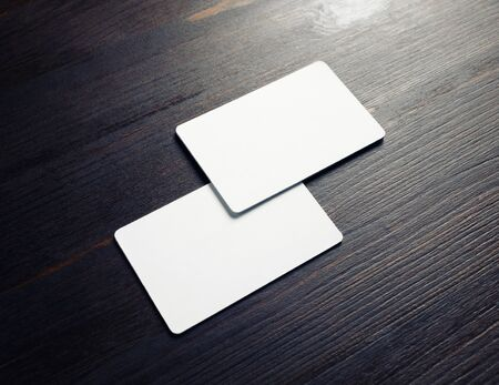 Photo of two blank white business cards on wooden background. Branding ID template.