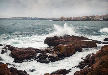 Sea waves crash on a rocky shore. Seascape in cloudy weather.