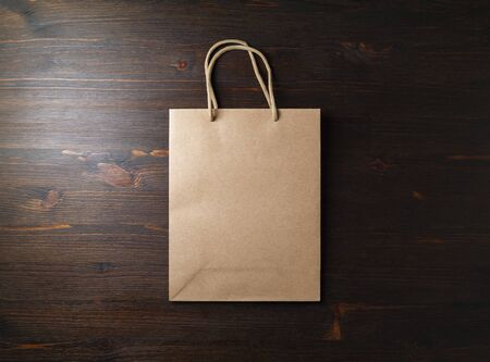 Blank brown paper bag with rope handles on wooden background. Flat lay.