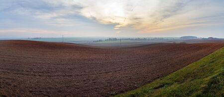 Panorama of arable land. Agricultural rural landscape. Evening in the countryside. Panoramic shot.