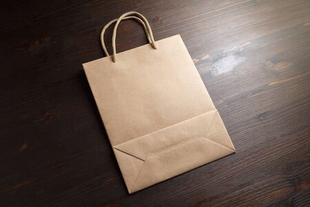 Blank brown paper shopping bag with rope handles on wooden background.