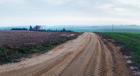 Gravel road in the countryside. Evening rural landscape. 스톡 콘텐츠
