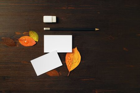 Photo of white business cards, pencil, eraser and bright autumn leaves on wooden background. Blank stationery template for placing your design. Foto de archivo - 135498369