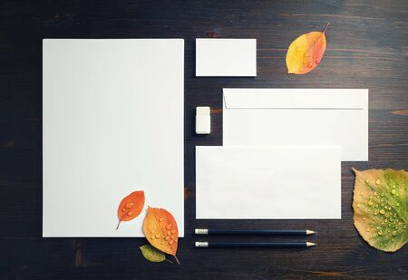 Photo of blank stationery set and autumn leaves on wooden background. Corporate stationery template. Flat lay. Foto de archivo - 135498626