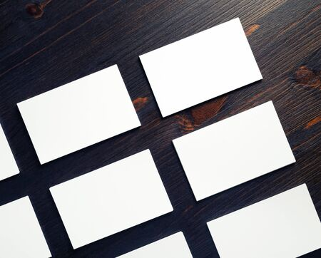 Blank white paper business cards on wood table background. Mock-up for branding ID. Flat lay. Foto de archivo - 135498653