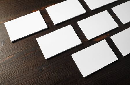 Photo of blank business cards on wood table background. Mockup for branding identity.