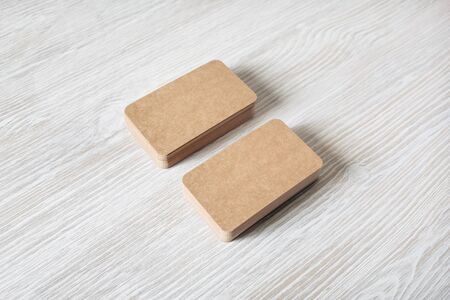 Photo of blank kraft business cards stacks on light wood table background. Template for branding identity.