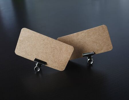 Two blank kraft business cards and metal binder clips on black wooden background. Mockup for branding identity.