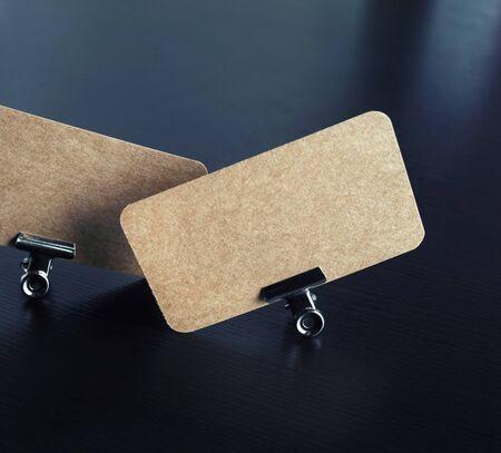 Photo of blank kraft business cards and metal binder clips on black wood table background. Reklamní fotografie