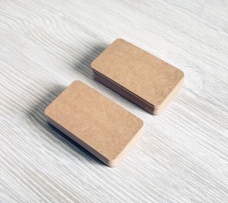 Two stacks of blank kraft paper business cards on light wooden background.