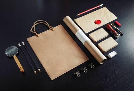 Photo of blank stationery set on black wood table background. Vintage corporate identity template. Responsive design mockup.