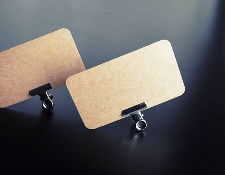 Blank vintage business cards in metal binder clips on black wooden background. Template for branding ID.