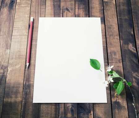 Blank white letterhead, pencil, eraser and cherry flowers on vintage wooden table background. Responsive design mockup.