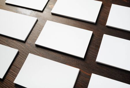 Photo of blank business cards on wood table background. Template for branding identity.