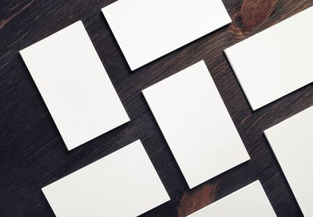 Blank white business cards on wooden background. Mock-up for branding identity. Blank template for design presentations and portfolios. Flat lay.
