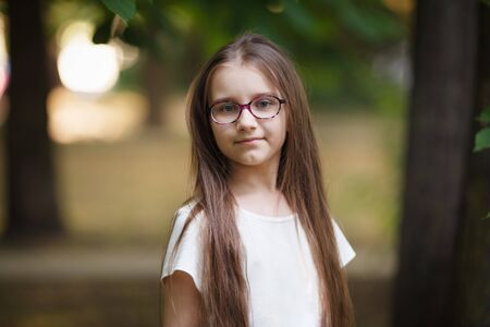 Child girl with long hair outdoors. Schoolgirl with glasses. Selective focus.