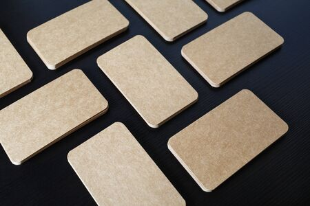 Photo of blank kraft paper business cards on black wooden background. Template for ID.