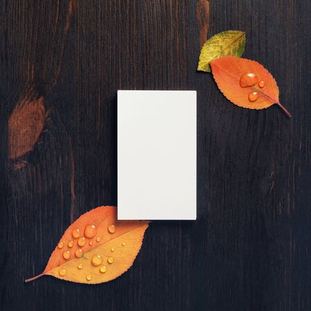 Blank business card and autumn leaves on vintage wooden background. Mock-up for ID. Blank template for branding identity for designers. Flat lay.