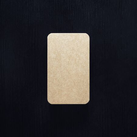 Blank vintage business card on black wood table background. Template for branding identity. Flat lay.