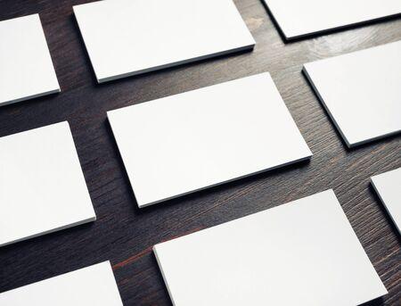 Blank white business cards on dark wooden background. Mockup for branding identity.