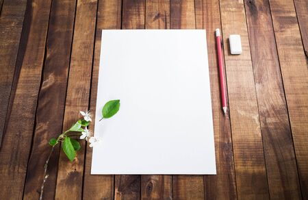 Photo of blank letterhead, pencil and eraser on wooden background. Responsive design mockup.