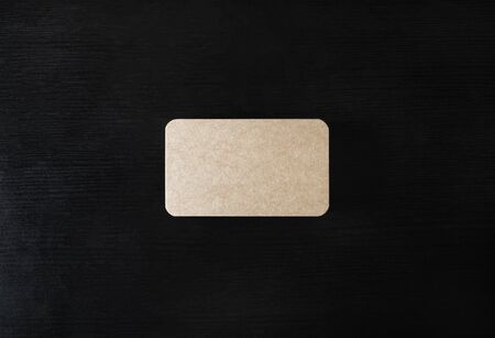 Photo of blank kraft business card on black wooden background. Mock-up for branding identity. Flat lay.