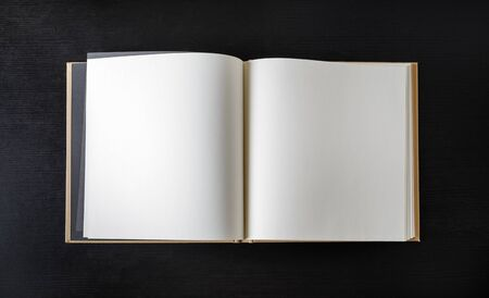 Open blank book on black wood table background. Flat lay.