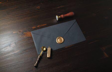 Enveloppe noire vintage avec sceau de cire doré, timbre et cuillère sur fond en bois. Banque d'images