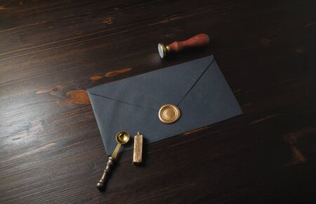 Vintage black envelope with golden wax seal, stamp and spoon on wooden background.