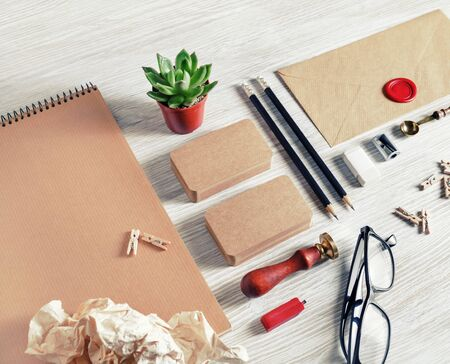 Blank kraft paper stationery set on light wood table background. Template for branding identity. For graphic designers presentations and portfolios.